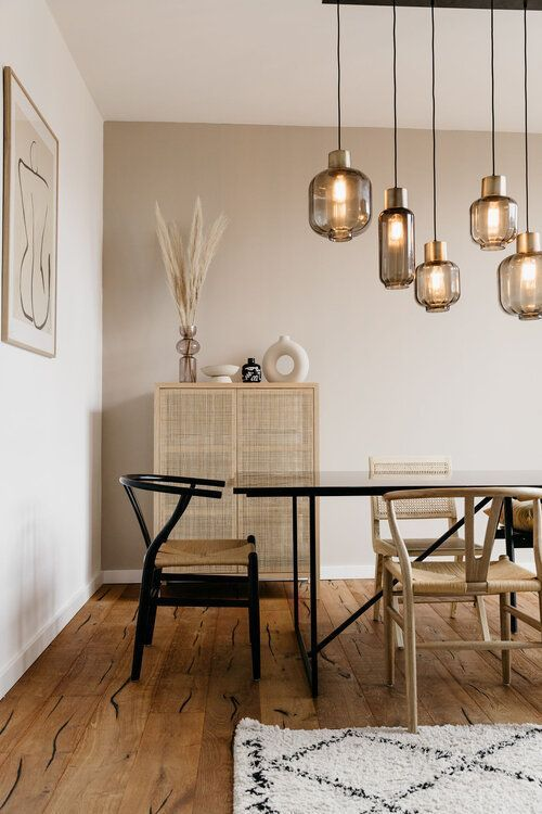 a cozy and warm dining room with greige walls, a black dining table, woven chairs, pendant lamps, a rattan cupboard and some pretty decor
