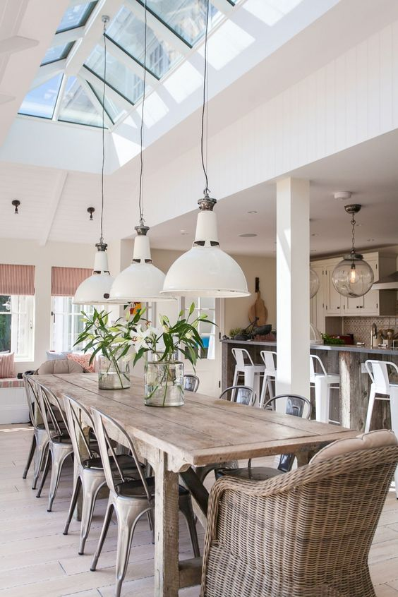 a cozy dining space with a rustic wooden table, a rattan chair and metal chairs with skylights above