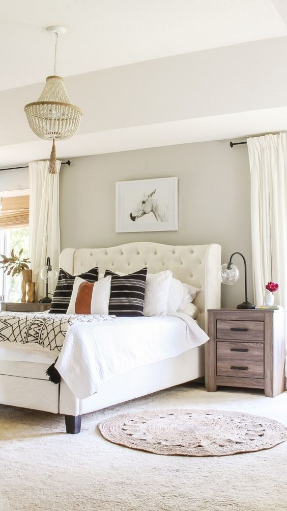 a cozy farmhouse bedroom with greige walls, a creamy upholstered bed, stained nightstands, neutral and printed bedding, a wooden bed chandelier and neutral curtains