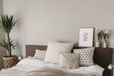 a cozy greige bedroom with a dark upholstered bed, potted plants and blooms, a white nightstand and printed bedding is inviting