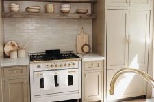a cozy greige kitchen with shaker cabinets, white stone countertops and a white skinny tile backsplash, reclaimed wood built-in shelves and gold fixtures