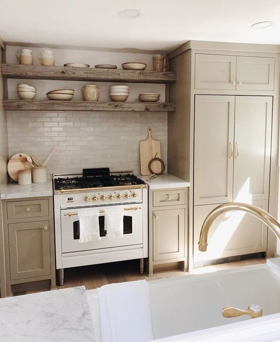 a cozy greige kitchen with shaker cabinets, white stone countertops and a white skinny tile backsplash, reclaimed wood built in shelves and gold fixtures