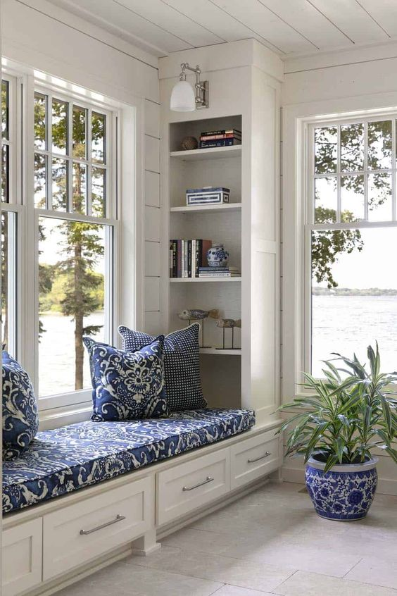 a cozy windowsill reading space with an upholostered windowsill bench with storage, built-in bookshelves and sconces