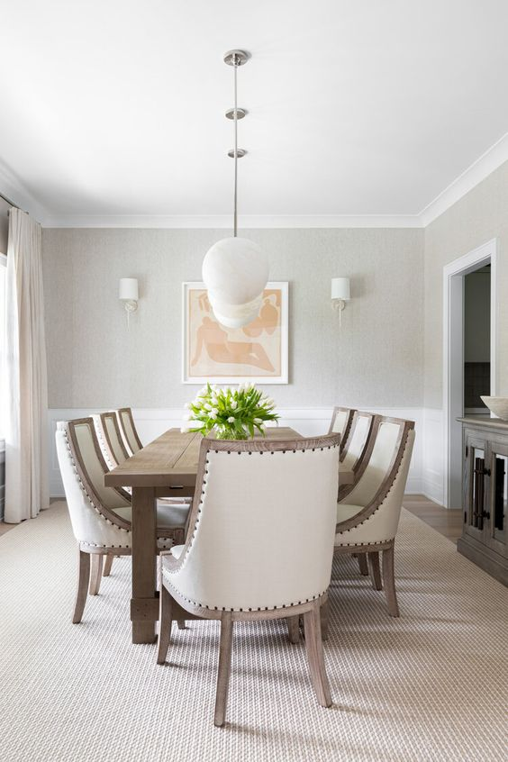 a delicate greige farmhouse living room with greige walls, white paneling, a wooden dining table, creamy upholstered chairs and a dark stained credenza