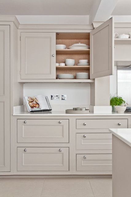 a delicate greige kitchen with shaker cabinets, white stone countertops and a matching sleek backsplash, simple knobs is a lovely idea