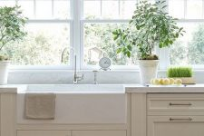 a delicate greige kitchen with shaker cabinets, white stone countertops, vintage fixtures and a window row as a backsplash is subtle and pretty
