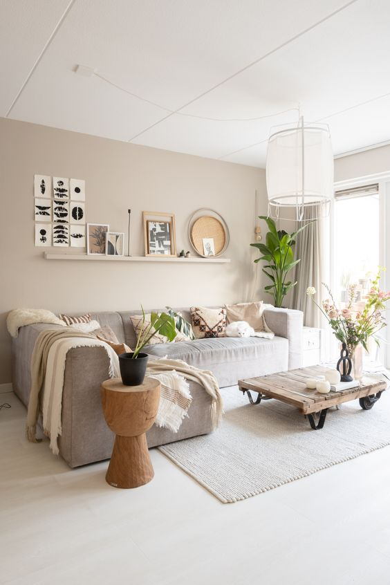 a delicate greige living room with a long ledge with a gallery wall, a grey sectional, an industrial coffee table and a wooden side table