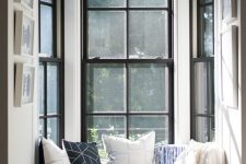 a double-height bow window with a small windowsill and a built-in seat with a cushions and pillows is a lovely nook to spend time