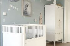 a dreamy Scandi nursery with pale blue walls and an accent one, white furniture, pendant lamps and a mobile plus toys