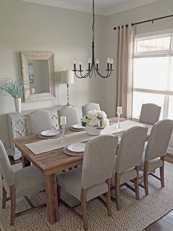 a dreamy greige dining room with a wooden dining table, neutral chairs, a black chandelier, a mirror in a whitewashed frame and a neutral sideboard