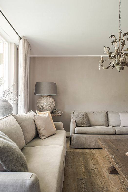 a dreamy greige living room with neutral sofas, a catchy chandelier, a table lamp and a large vase with branches plus a wooden coffee table