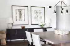 a farmhouse dining room with reclaimed wooden beams, a black credenza, a greige dining table and white chairs plus a black chandelier
