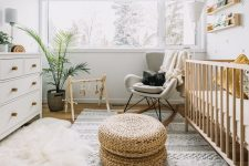 a fresh and inviting Scandi nursery with a wallpaper wall, a large stained crib, a grey rocker, a white dresser, layered rugs, open shelves