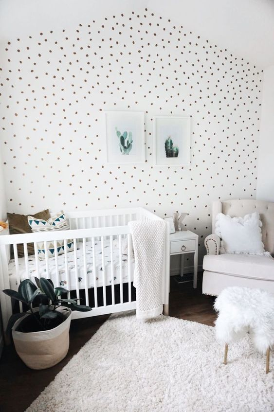 a fresh neutral nursery with a spotted accent wall, white and creamy furniture, a neutral rug and bedding, a mini gallery wall