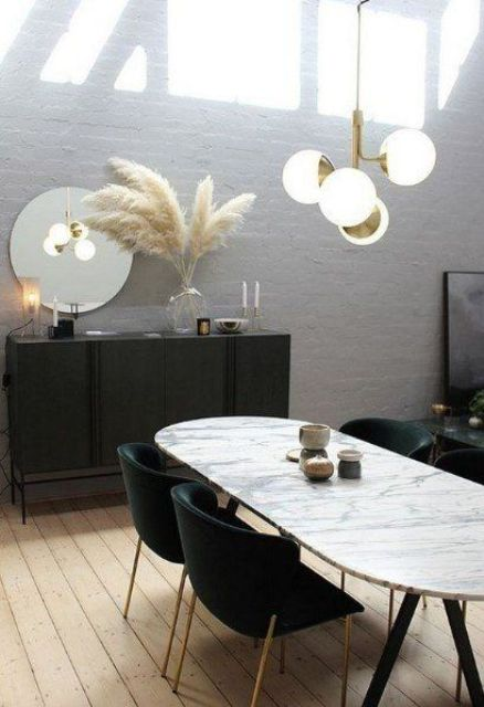 a gorgeous dining room with greige walls, a black credenza, a marble oval table, black chairs, a gilded chandelier and pampas grass