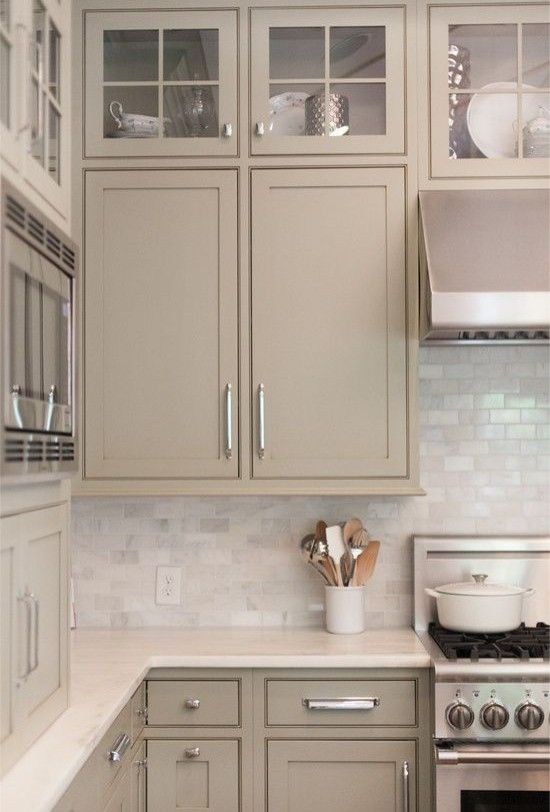 a gorgeous greige kitchen with shaker and glass frame cabinets, a white marble subway tile backsplash and shiny handles