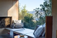 a gorgeous windowsill reading space with a leather couch, open bookshelves and pillows by a panoramic window