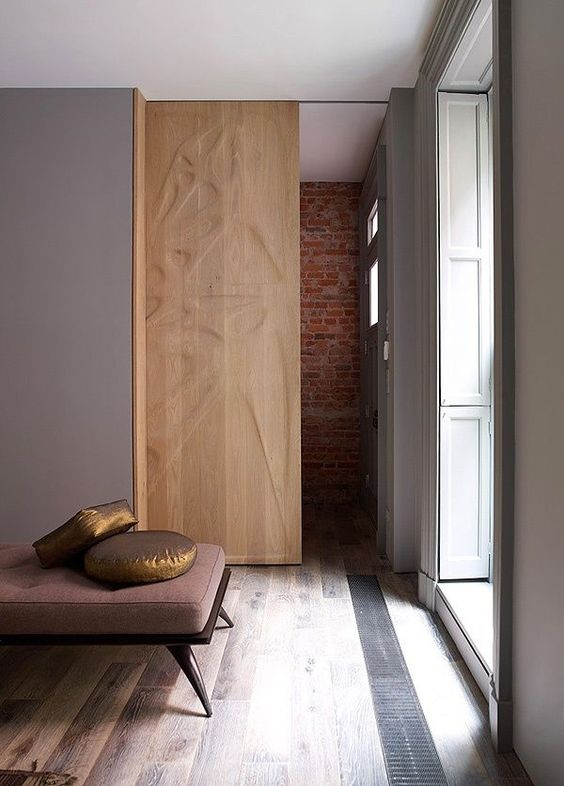a gorgeous wooden pocket door with a pattern is a beautiful decor feature that separates the space in a cool way