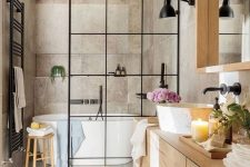 a greige bathroom clad with concrete, with a light-stained vanity and a large mirror, a shower space with a black space divider and black fixtures
