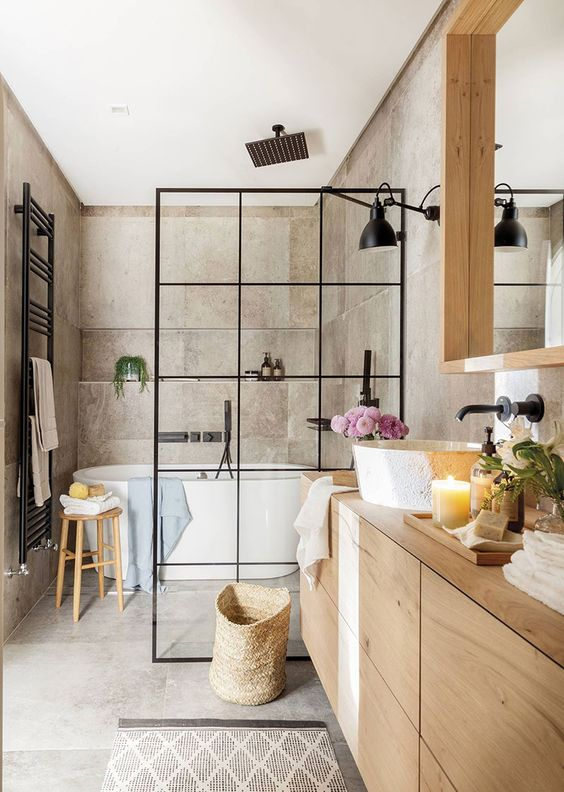 a greige bathroom clad with concrete, with a light stained vanity and a large mirror, a shower space with a black space divider and black fixtures