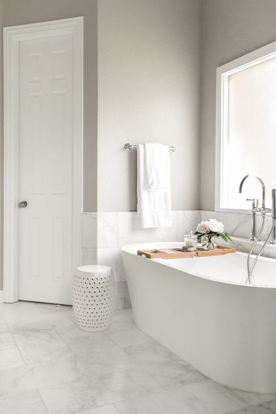 a greige bathroom with white marble tiles, an oval tub by a frosted glass window, a side table and a bathtub caddy is cool