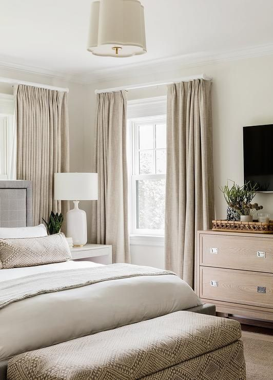a greige bedroom with a grey upholstered bed, a stained dresser, beige curtains and an upholstered storage bench plus bedding