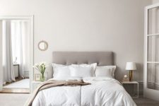 a greige bedroom with a grey upholstered bed, neutral bedding, a floor to ceiling mirror, matching white nightstands and table lamps