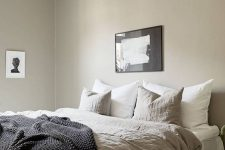 a greige bedroom with a large bed, lightweight nightstands, a beautiful pendant lamp and some lovely black and white artworks