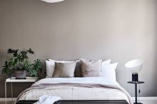 a greige bedroom with a pretty bed, mismatching nightstands, a potted plant, a black bench and neutral bedding is amazing