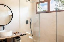 a greige contemporary bathroom with a shower space enclosed in glass, a floating open shelf vanity, a round mirror in a black frame, black fixtures