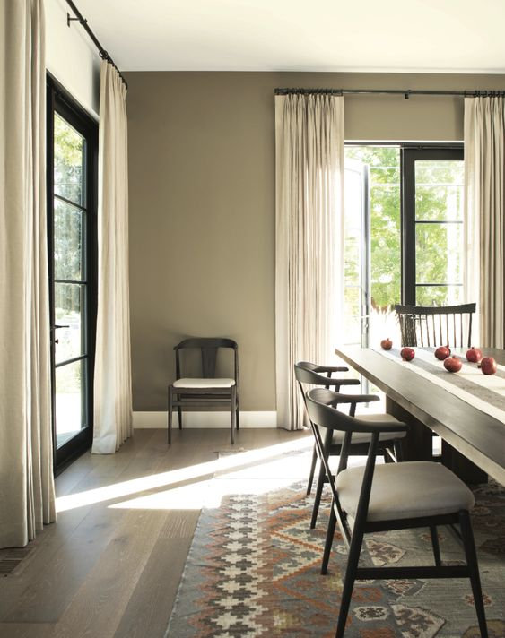 a greige dining room with a black long dining table, neutral and black chairs, neutral curtains, a bold printed rug is a lovely space to have a meal