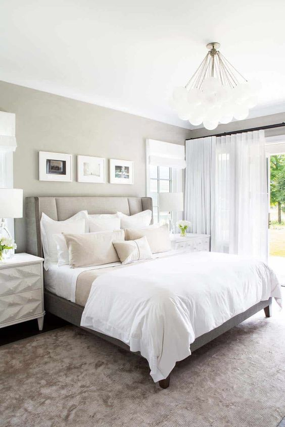 a greige farmhouse bedroom with a greige bed, neutral bedding, geometric nightstands, pendant and table lamps and a mini gallery wall