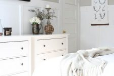 a greige farmhouse bedroom with white paneling, white furniture and textiles, mini artworks and some pretty decor and accessories
