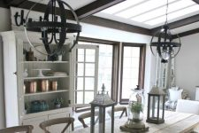 a greige farmhouse dining room with dark stained wooden beams, a whitewashed wooden dining set, an elegant buffet and sphere chandeliers