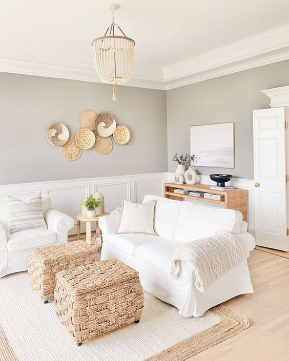 a greige farmhouse living room with paneling, white seating furniture, woven storage poufs, decorative baskets and a credenza is a chic space