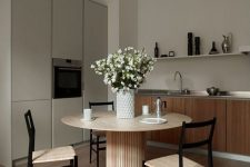 a greige kitchen combined with a kitchen, light-stained furniture, a round table and woven chairs, a grey storage unit, a long shelf and some blooms
