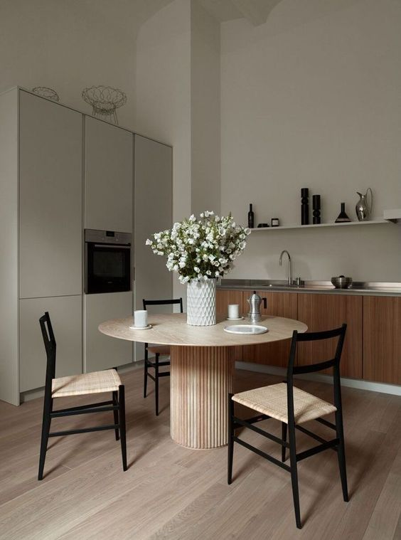 a greige kitchen combined with a kitchen, light stained furniture, a round table and woven chairs, a grey storage unit, a long shelf and some blooms