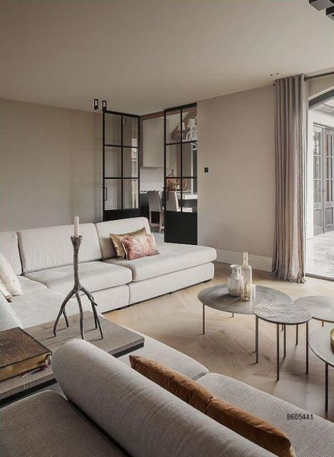 a greige living room with a large neutral sectional, round hammered coffee tables and mustard pillows is an ethereal and lovely space