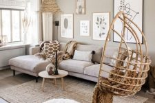 a greige living room with a neutral sectional, a gallery wall, a pendant egg chair, a woven lamp and some jute is a cozy space