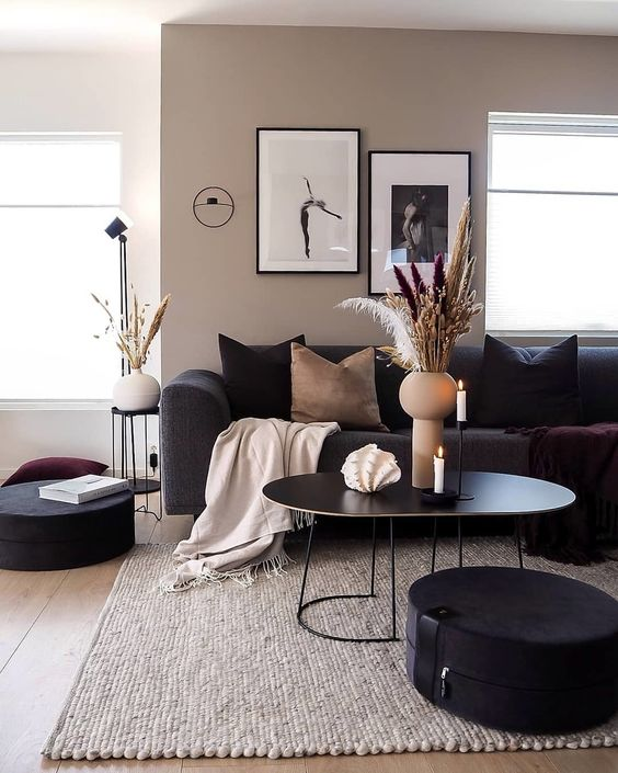 a greige living room with black seating furniture, a black coffee table, a mini gallery wall, black and tan pillows, a terracotta vase and some grasses