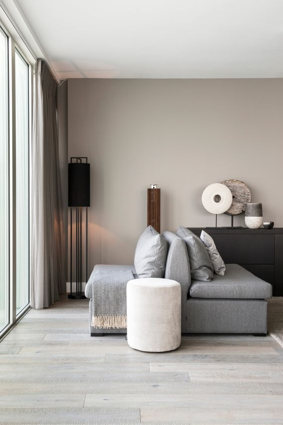 a greige living room with grey furniture, a black credenza, some floor and table lamps, greige curtains is a cozy and soothing space