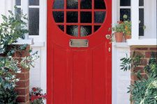 a hot red front door with glass panes and refined metal touches, with greenery and bold red blooms that echo with the door