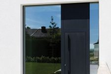 a large and a narrow window plus a black metal front door with an oversized handle on it is a cool solution for a modern house