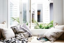 a large window with a built-in daybed with a tan cushion and lots of printed pillows and a blanket with pompoms form a cool reading nook