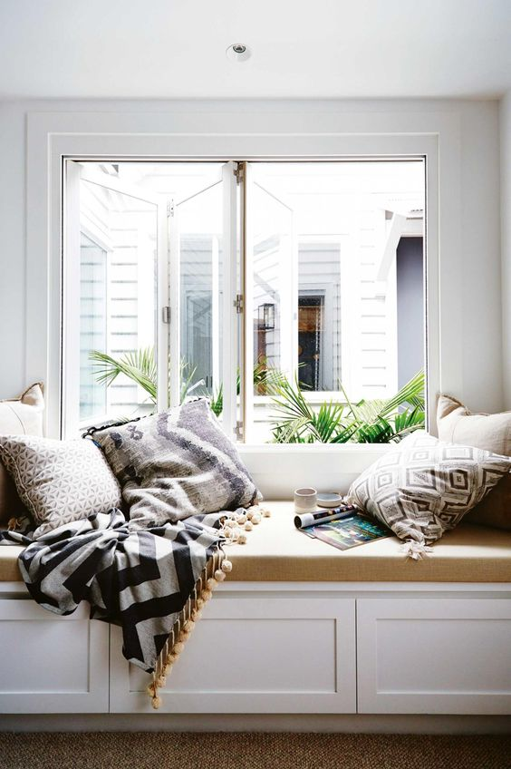 a large window with a built in daybed with a tan cushion and lots of printed pillows and a blanket with pompoms form a cool reading nook