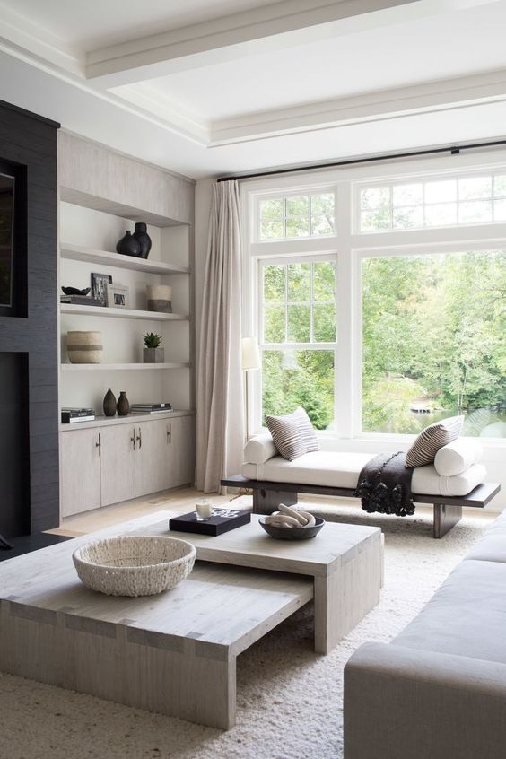a light filled greige living room with built in storag eunits and shelves, a bench, a dup of coffee tables and a greige sofa plus a black fireplace