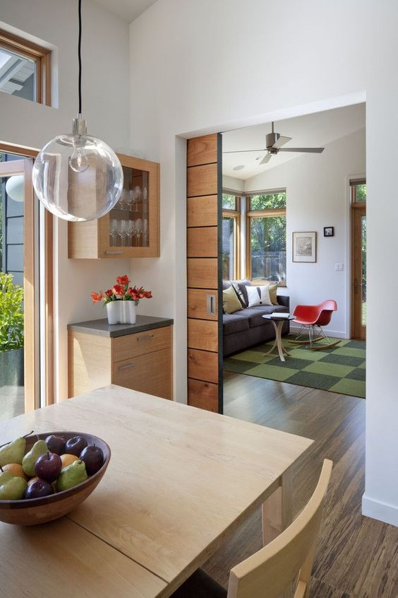a light stained pocket door leading to a dining room is a cool addition to a mid-century modern interior and it adds a warm touch