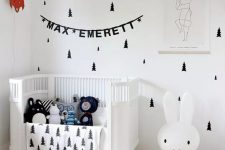 a lovely Scandi nursery with tree decals, a white crib, an iconic Miffy lamp, some art and lots of toys