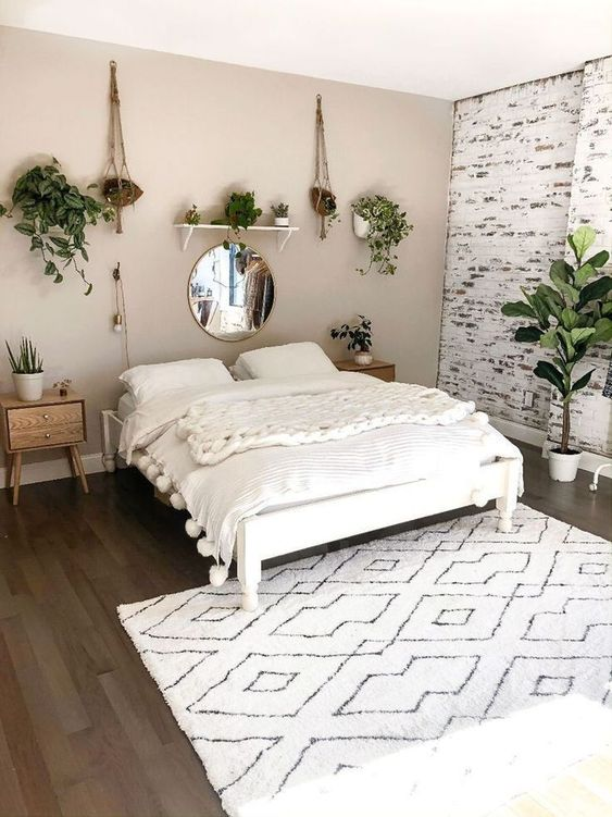 a lovely bedroom with a greige accent wall and a whitewashed brick one, a white bed with creamy bedding, stained nightstands and potted greenery