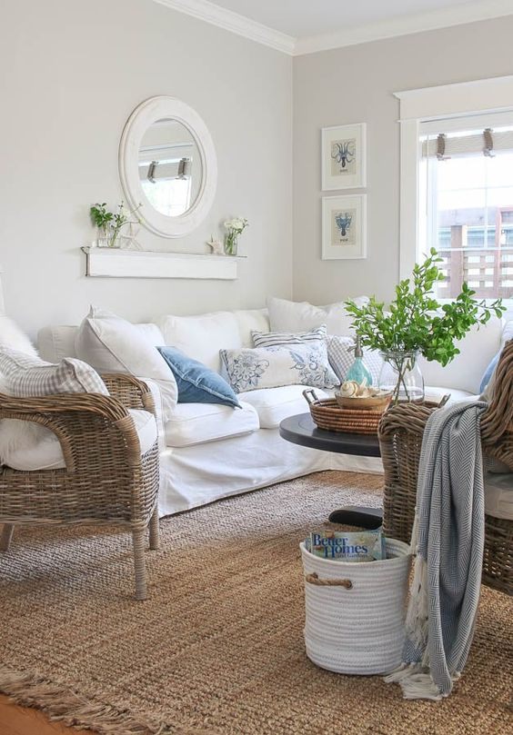 a lovely greige farmhouse living room with a white sectional, woven chairs, a mini gallery wall, a round mirror and printed pillows